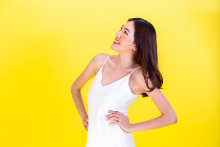 Asian cute woman posing arms akimbo or hands on hips isolated on yellow background Archivio Fotografico