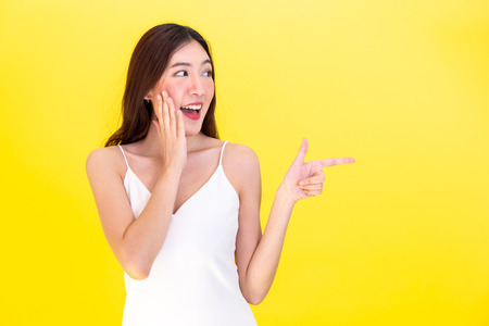Asian beautiful woman surprised and shocked with smile and pointing at empty copy space over yellow background