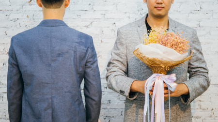 Gay couple holding a bouquet of flowers, ready to give to his partner for special occasions or wedding proposal. Asian homosexual men together Stock Photo