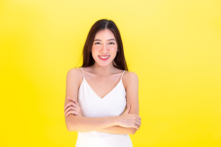 Asian beautiful woman standing arms folded with confidence and empty copy space over yellow background