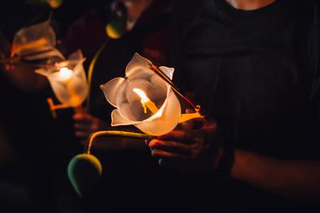 Buddhistisches Beten mit Räucherstäbchen, Lotusblume und Kerzen am heiligen Religionstag von Vesak in der Nacht
