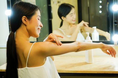 Young Asian girl in spaghetti strap tank top applying sunscreen lotion all over body Stock Photo