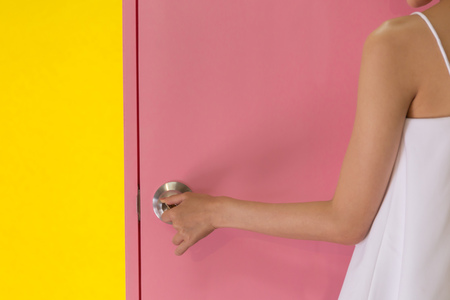 Close up of woman hands on metal door knob of pink closed door over yellow background Stock Photo