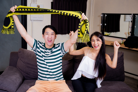 Asian man and woman watching and cheering football soccer raising up with scarf on the couch at home