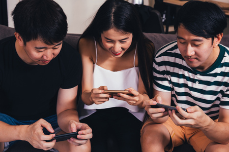 Group of young Asian people sitting and addicted to playing mobile online games together at indoors Archivio Fotografico