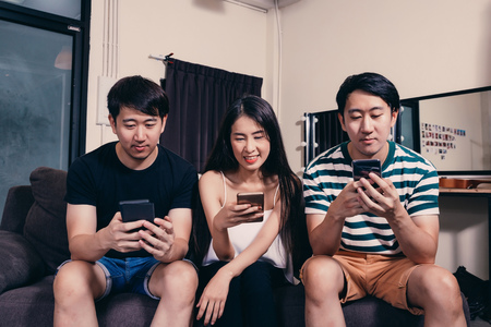 Group of young Asian people addicted to playing smart phone sitting at home Stock Photo