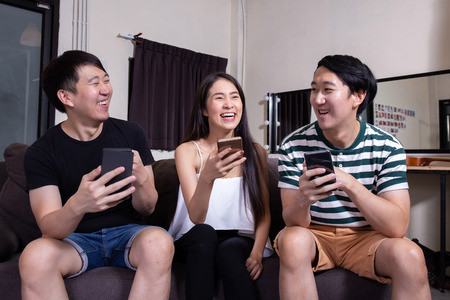 Group of young Asian male and female people smiling and laughing together as using their smart phone at indoors home