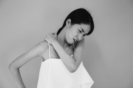 Asian woman having chronic neck and shoulder pain in black and white tone - Healthcare and Medical concept