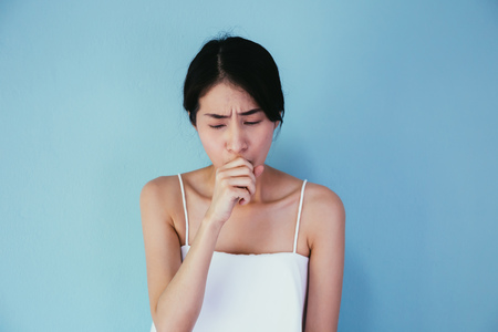 Young Asian woman suffering from cough  lung or throat problems isolated over blue background - Healthcare and Medical concept