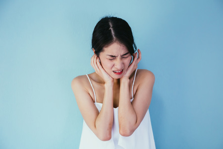 Young Asian woman having earache or ear pain isolated over blue background - Healthcare and Medical concept