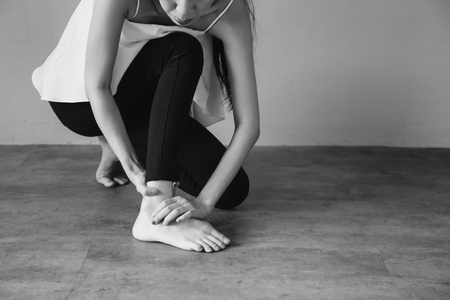 Young woman having ankle pain in black and white tone - Healthcare and Medical concept