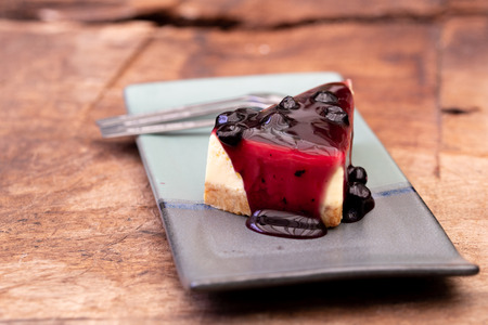 Tasty and delicious cheesecake dessert with berry fruit made on top served plate on wooden table