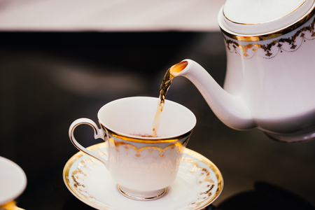 Hot healthy tea being poured from old style classic jug into the tea cup