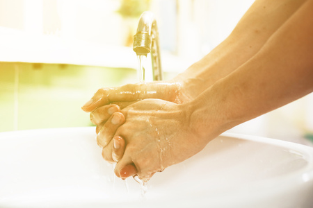 Close-up of human hands washing away germs and bacteria under the sanitary crane