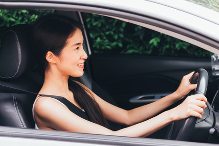 Young attractive Asian woman in casual wear looking at the road and driving a car Stock Photo