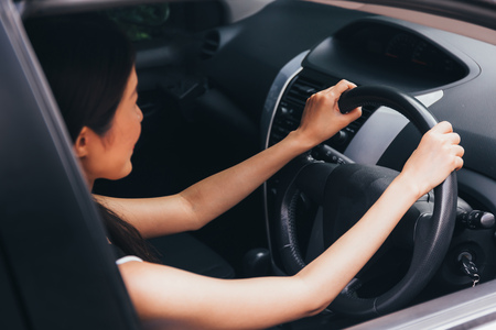 Rear view of young attractive Asian woman in casual wear looking at the road and driving a car Stock Photo