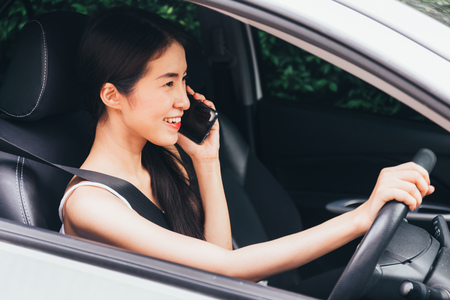Young Asian woman calling and using a smart phone while driving a car. Dangerous and risky driving concept Stock Photo
