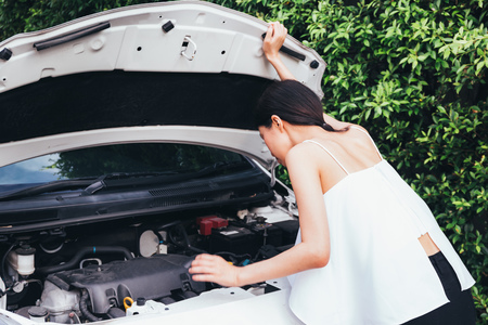 Asian woman checking her broken car and failed engine on roadside