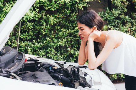 Asian woman frustrated and angry checking her broken car and failed engine on roadside