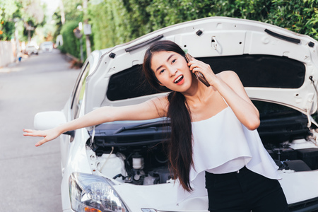 Young desperate Asian woman calling for assistance help or hitchhiking in car breakdown situation