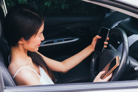 Young Asian woman multitasking and using two smart phones while driving a car. Dangerous and risky driving concept