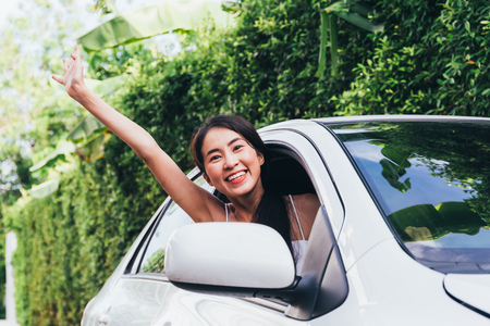 Young Happy Asian woman smiling and waving from drivers seat in car while taking on journey travel