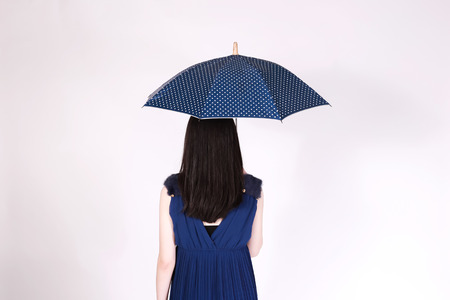 Rear view of business woman back holding an opening umbrella in white isolated background Stock Photo