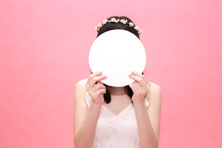 Young fashionable woman holding an empty circle paper covering on face - with blank copy space used to insert any text and advertising
