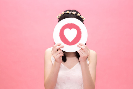 Young fashionable woman holding love symbol over her own face in pink background