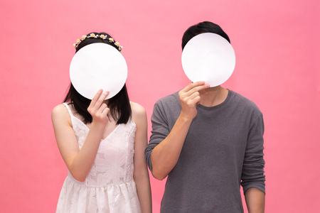 Man and woman as couple hiding face from empty and blank round bubble speech - with copy space to insert anything