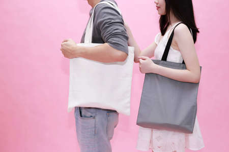Young male and female couple using an empty blank tote cotton bag together in pink background - with copy space to insert anything