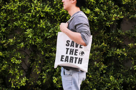 Young male hipster holding and carrying the Save The Earth tote handbag in green nature environment background - ecology and recycle concept Standard-Bild