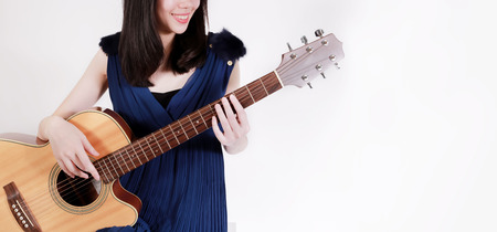 Young teenage woman playing a acoustic guitar isolated over white background - with copy space for ads and banner