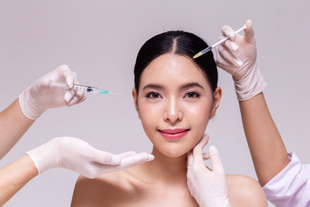 Mixed Asian young 20s woman going through skin care and aesthetic medical therapy and to be injected by hands of doctor with syringes in white background