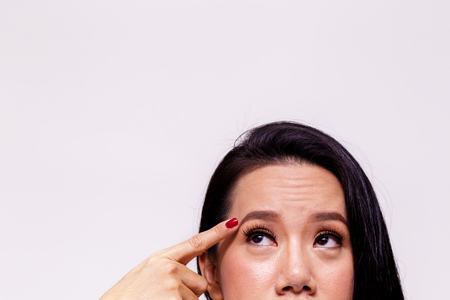 Asian young woman worried and pointing finger towards her aging and old forehead - with copy space - treatment skin care concept Banco de Imagens