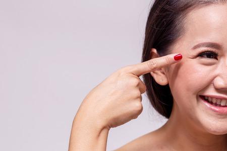 Bella donna asiatica adulta che sorride mentre diteggia e indica le rughe intorno agli occhi di invecchiamento nella priorità bassa bianca - con lo spazio della copia Archivio Fotografico