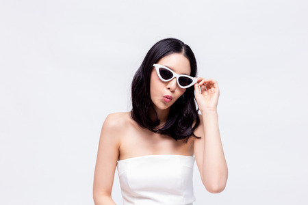 Elegante und attraktive asiatische schicke Modefrau im stilvollen weißen Kleid mit Sonnenbrille im isolierten Hintergrund