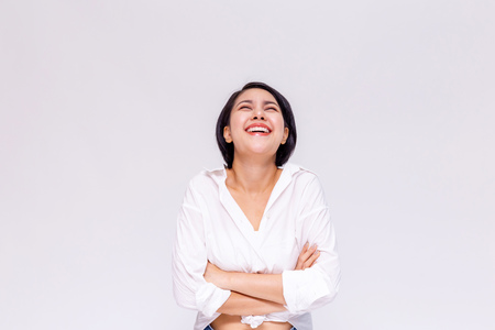 Young beautiful and confident Asian girl with short hair arms crossed with joy and happiness in white isolated background Stockfoto