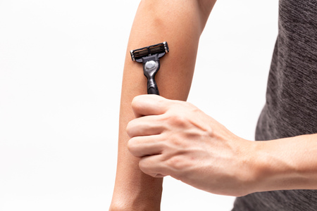 Part of human body arm using razor to shave and remove arm hair in white isolated background Stock Photo