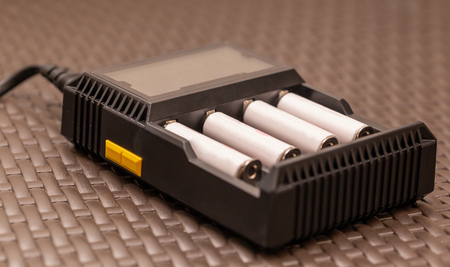 Stack of rechargeable AA batteries being recharged - Close up shot