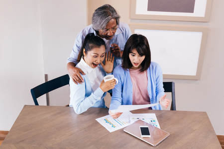 Happy Asian family reading and receiving a good news letter together at home Stockfoto - 105388696