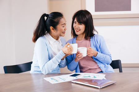 Asian family of middle aged woman and young teenage daughter talking and smiling at coffee shop
