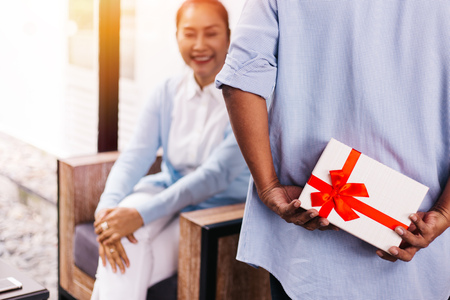 Middle aged husband hiding a surprise gift and roses for surprising his wife on special day such as birthday or wedding anniversary. Celebration and holiday concept