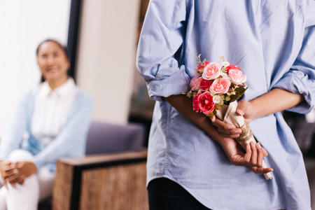 Teenage daughter hiding a surprise bouquet of roses and giving to senior mother on her special day such as mothers day or birthday. Celebration and holiday concept