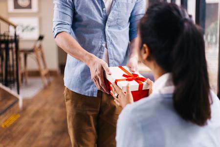 Vriend geeft een verrassingsgeschenk aan zijn vriendin op haar speciale dag, zoals verjaardag. Viering en vakantieconcept Stockfoto