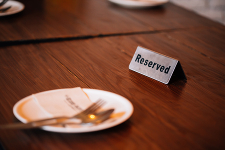 Reserved Sign on dining table in restaurant with spoon, fork and plate