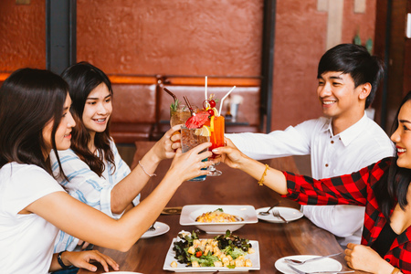 Group of Asian happy and smiling young man and women holding an alcoholic cocktail for toasting and celebrating in social party in restaurant Stock Photo - 105388673