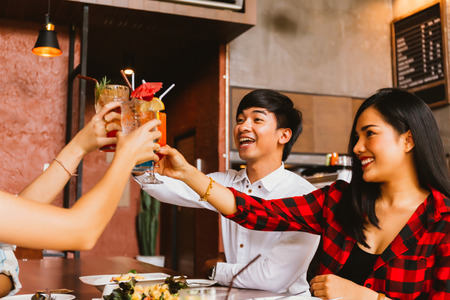 Group of Asian happy and smiling young man and women holding an alcoholic cocktail for toasting and celebrating in social party in restaurant Imagens