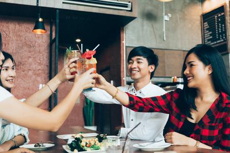Gruppe von asiatischen glücklichen und lächelnden jungen Mann und Frauen, die einen alkoholischen Cocktail zum Anstoßen und Feiern in der sozialen Partei im Restaurant halten