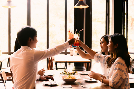Group of Asian happy and smiling young man and women holding an alcoholic cocktail for toasting in restaurant against sunset